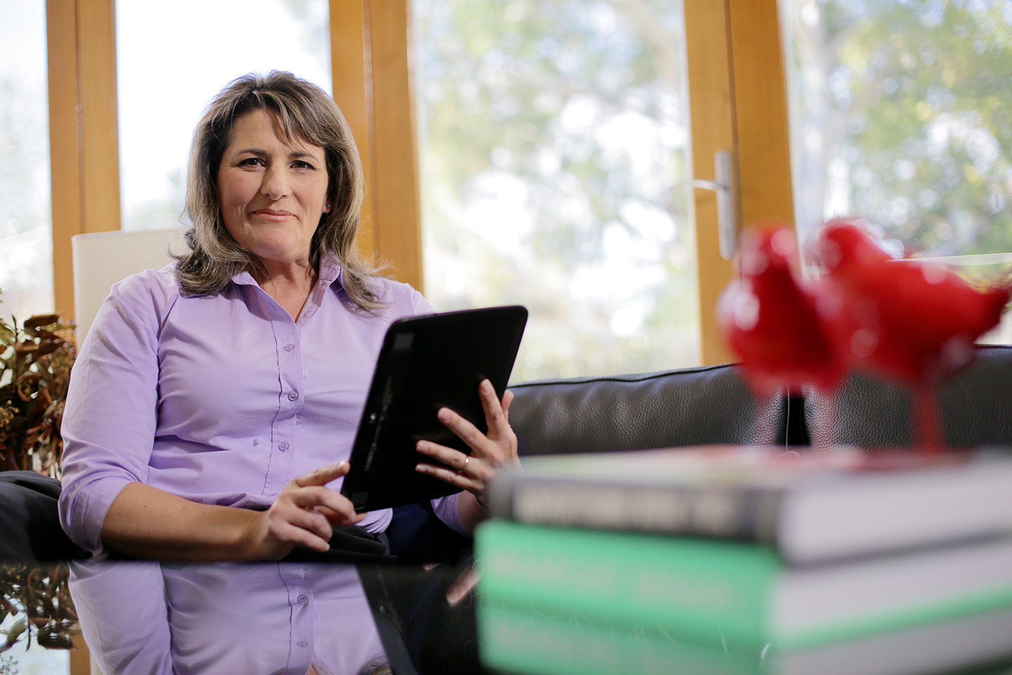 Woman holding mobile device at desk